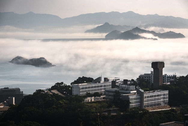 Buildings surrounded by trees, water and mountains covered in fog