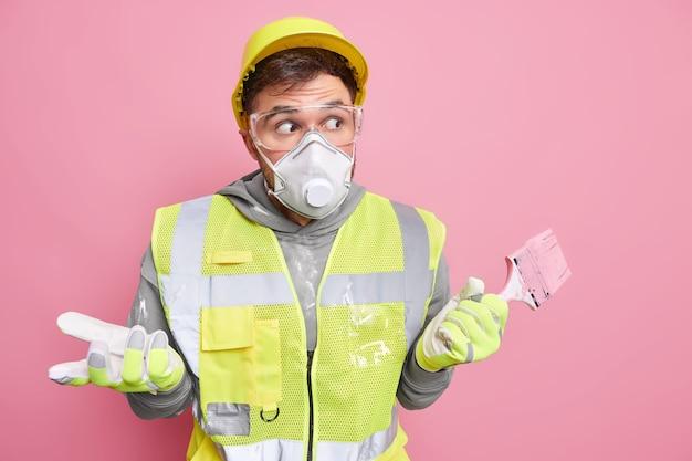 建物の改良と改装のコンセプト。作業服を着た困惑した躊躇する便利屋が絵筆を持ってピンクの壁に無知な驚きの表情ポーズ。ショックを受けた修理工