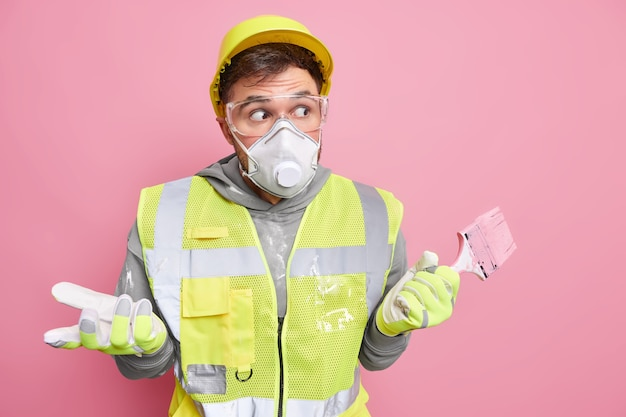 Buillding improvement and redecoration concept. puzzled hesitant handyman in working clothes holds paint brush has clueless surprised expression poses against pink wall. shocked repairman