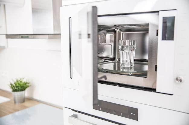 깨끗한 물 한 컵과 함께 주방에 빌트인 전자 레인지.