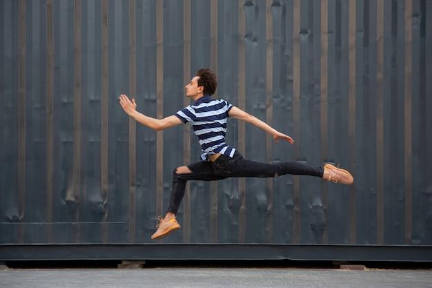 高いジャンプで走る、建物の前で若いbuinessmanをジャンプ