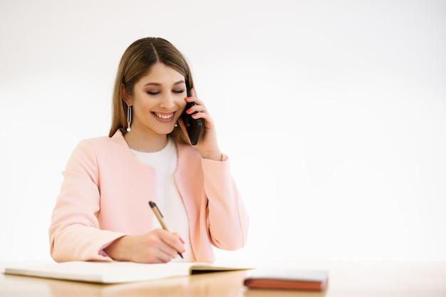 솔직한 미소를 지닌 buinesswoman은 전화로 채팅하고 카페에서 커피 브레이크를 즐기고 있습니다. 캐주얼 흰색 스웨터 핑크 jaket 입고