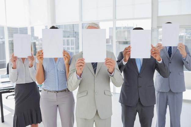 비즈니스 팀은 빈 페이지를 들고 그들의 얼굴을 덮고