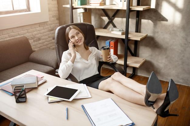 肯定的な幸せな若いbuisnesswomanはテーブルに座って電話で話します。彼女はテーブルの上に足を保持します。モデルに破損があります。彼女は見上げる。
