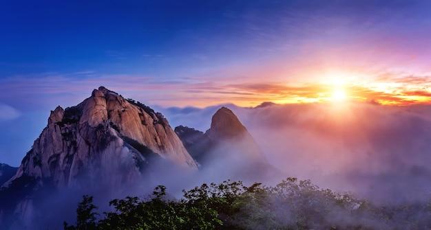 韓国のソウルにある北漢山国立公園では、北漢山の山々が朝霧と日の出に覆われています。