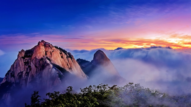 韓国のソウル、北漢山国立公園の北漢山は朝霧と日の出に覆われています