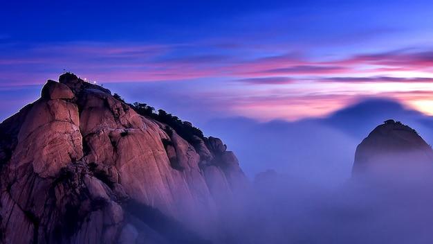 북한산은 한국 서울의 북한산 국립 공원에서 아침 안개와 일출로 덮여있다.