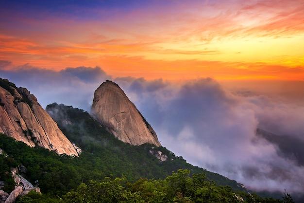 韓国、ソウルの北漢山は朝霧と日の出に覆われています