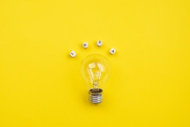 次の碑文のアイデア黄色のテーブル上の電球