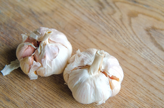 Bulbs of organic garlic and garlic cloves on natural wooden background