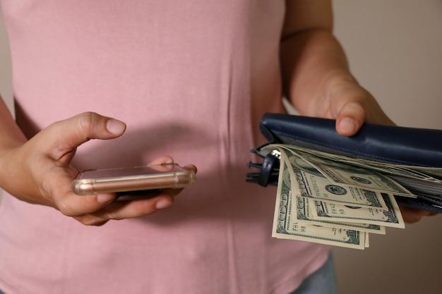 女性の手の中には数百ドルの札束とスマートフォンが付いているbuleの革財布が