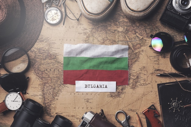 Bulgaria flag between traveler's accessories on old vintage map. overhead shot