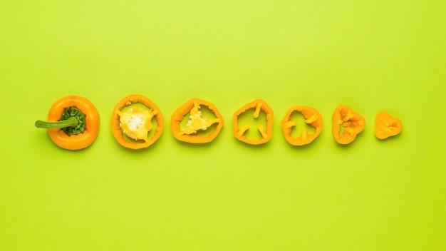 Болгарский перец нарезать кусочками на зеленом фоне. вегетарианская пища.