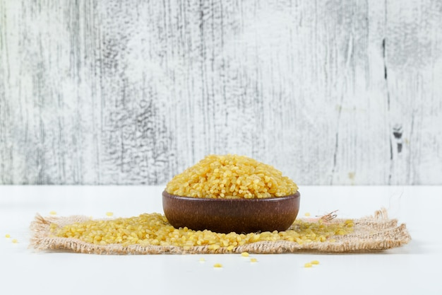 Bulgur cereal in a bowl on piece of sack side view on grunge and white background