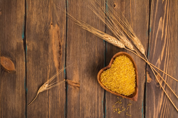 Bulgur grains with ears of wheat over grunge wooden background. top view