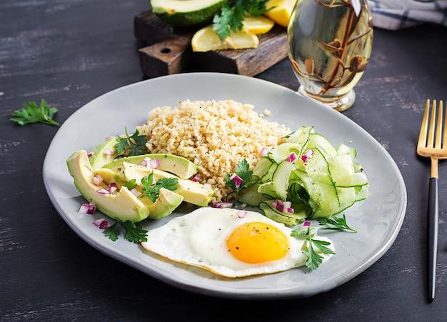 Булгур каша, жареные яйца и свежие овощи - огурец и авокадо на тарелке.