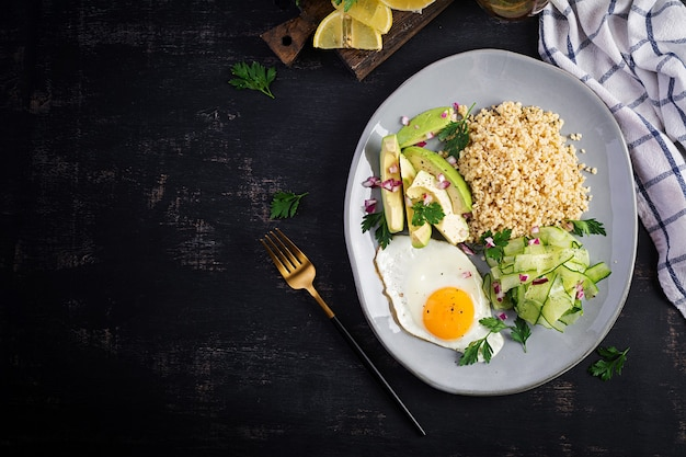 Bulgur porridge, fried egg and fresh vegetables -  cucumber and avocado on plate. top view, overhead, copy space