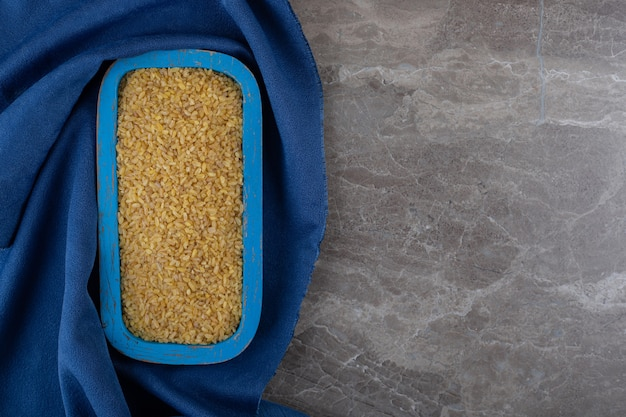 Bulgur in the tray on the towel ,on the marble surface