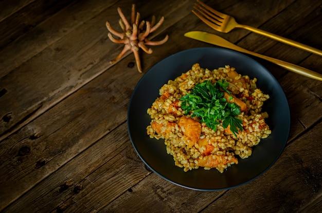 木製のテーブルにカボチャとブルガー。インド料理のベジタリアンレシピ。