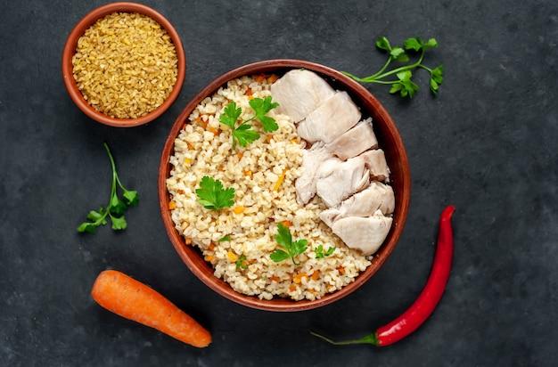 Булгур с овощами и курицей на миске