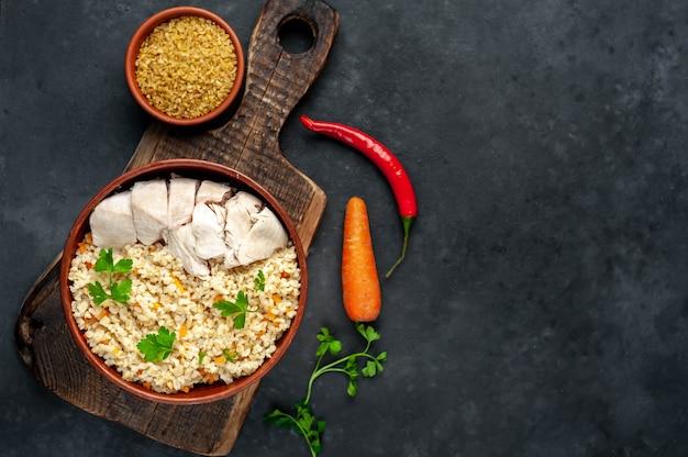 Булгур с овощами и курицей на белой тарелке