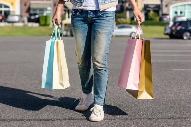 パステルのbulidingの背景で屋外のフリーマーケットを買い物する若いアジア人女性のクローズアップ