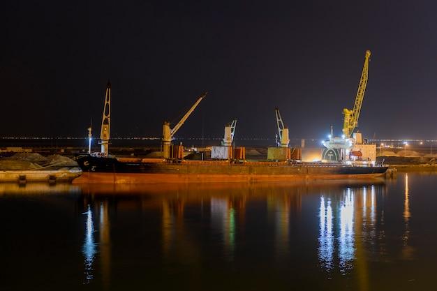 Балкер пришвартовался у причала в порту. ночной вид. bulker. сухогруз.