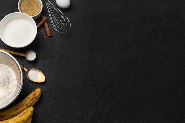 ボウルにバナナブレッドと黒の背景にバナナのバルク材料