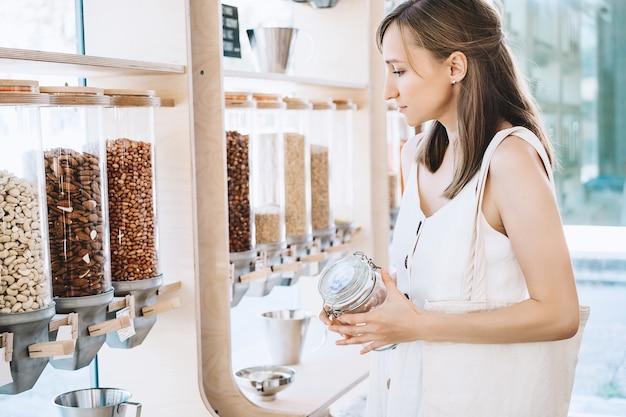 제로 폐기물 가게의 대량 제품 플라스틱 없는 식료품점에서 건조 제품을 사는 여성