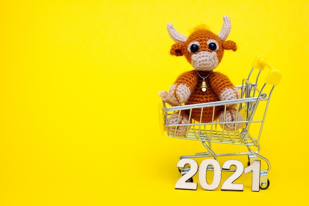 The bull is the symbol of the new year 2021. knitted toy bull in a supermarket toy cart.