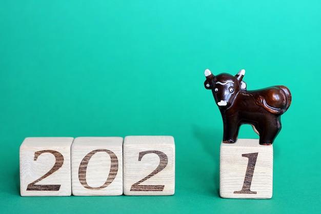Бык символ нового 2021 года. игрушечный коричневый бык расположен на деревянных блоках