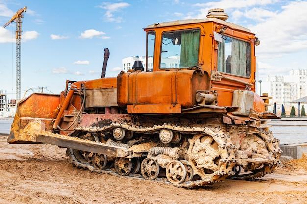 Бульдозерная машина выравнивает строительную площадку. землеройный комбайн с гусеницей перемещает землю. крупный план. строительная тяжелая техника.