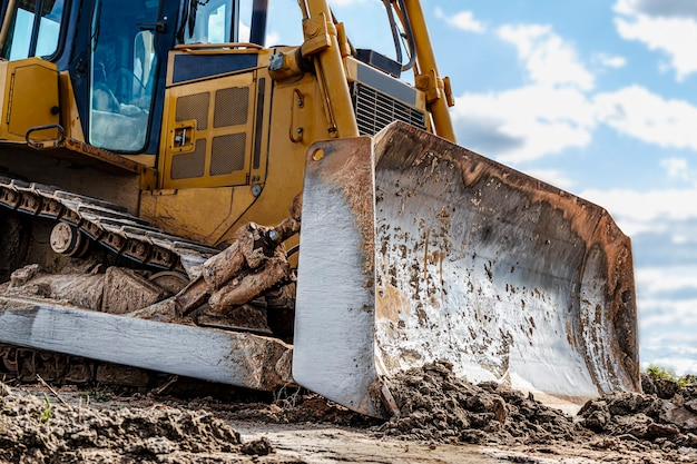 Bulldozer machine is leveling construction site. earthmover with caterpillar is moving earth. close-up. construction heavy machinery.