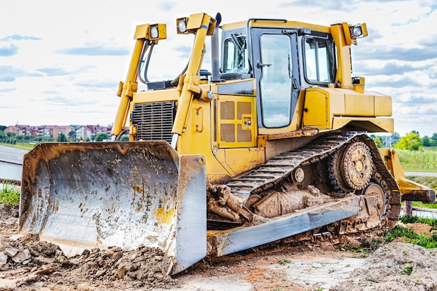Bulldozer machine is leveling construction site. earthmover with tractor is moving earth. close-up. construction heavy machinery.