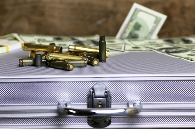 銀のケースの弾丸とお金のドル