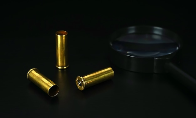 Bullet casings from a 38mm with blurry magnifying glass on dark background concept of investigatio