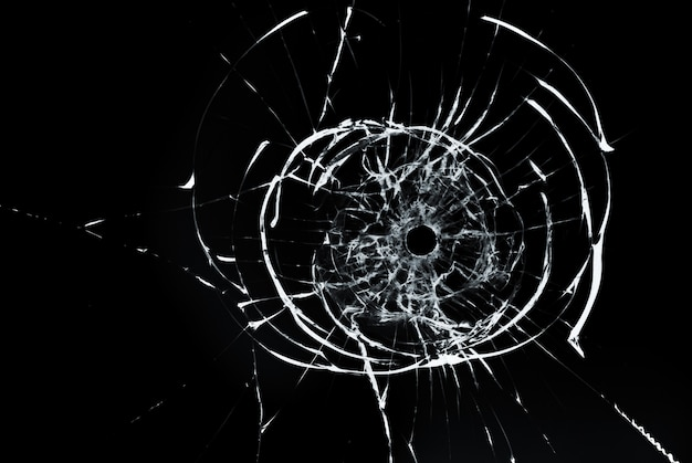 Bullet hole in glass close up on black background