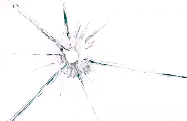 Bullet hole in glass close up on white background