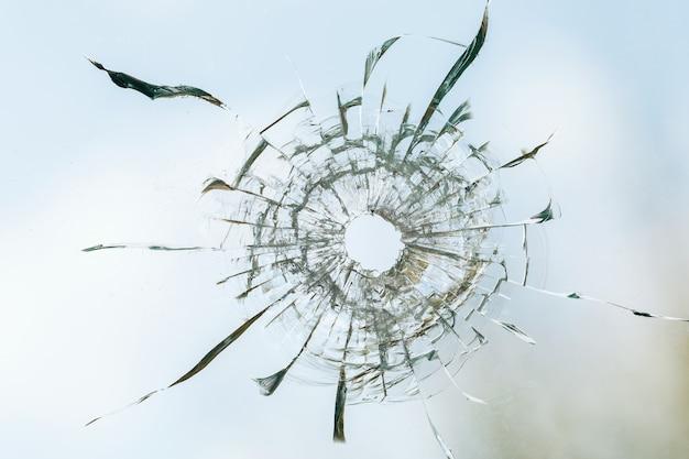 雲と空の背景に汚れたガラスの銃弾の穴