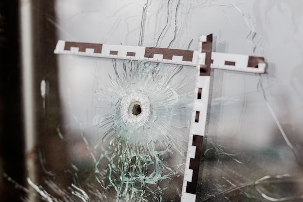 Bullet holes in a glass shop window marked with a police tape