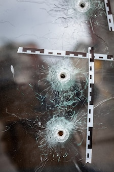 경찰 테이프로 표시된 유리 상점 창문의 총알 구멍