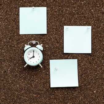 Доска объявлений с пустыми стикерами для планов и часами для контроля времени