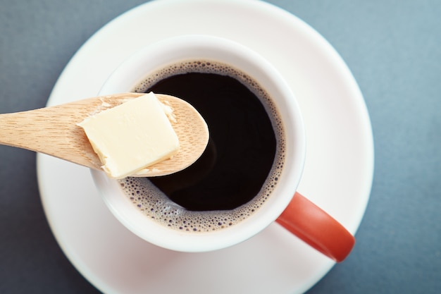 Bulletproof coffee, cup and butter in spoon