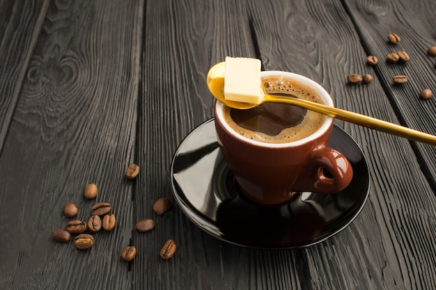 黒い木の表面に防弾コーヒーケトダイエットエネルギー飲み物。閉じる。