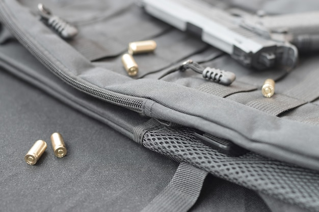 Пули и пистолет лежат на черном рюкзаке