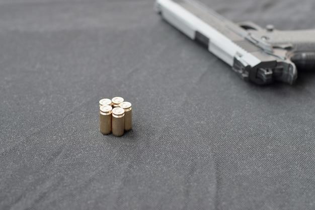 Пули и пистолет лежат на черной ткани