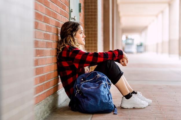 Запуганная девочка, сидящая одна в школе