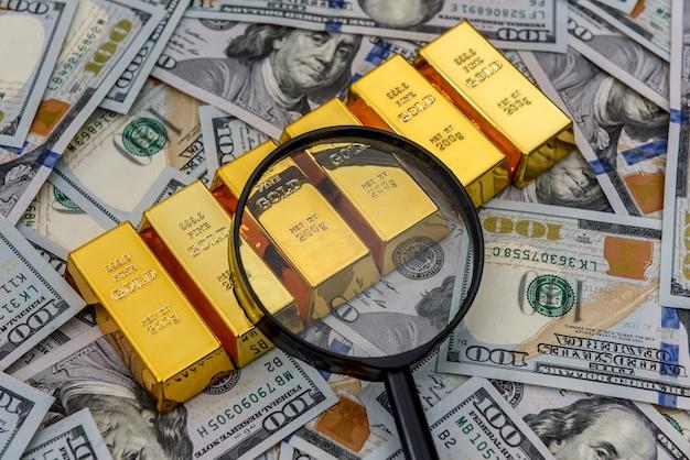 돋보기가있는 미국 달러 지폐의 덩어리, 금 또는 주괴