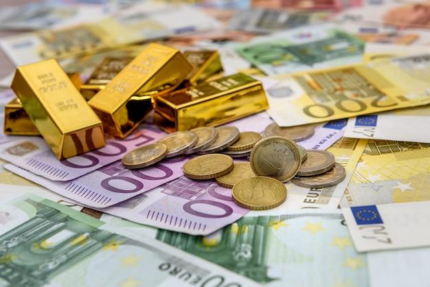 ユーロ紙幣の背景にユーロセント硬貨と地金