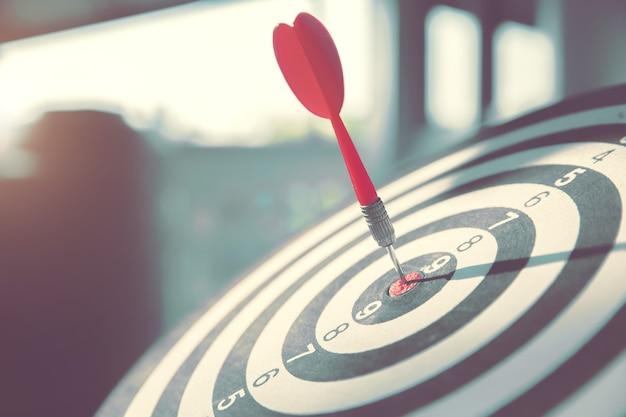 Bulls eye or dart board has red dart arrow throw hitting the center of a shooting target.
